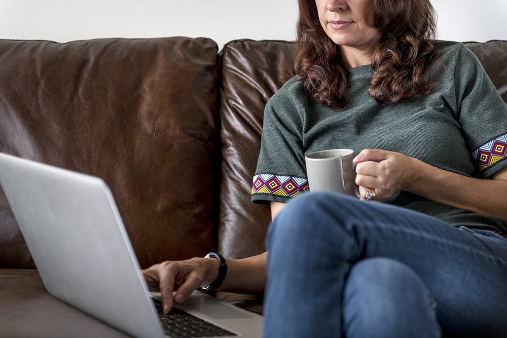 woman-using-laptop-on-sofa-in-the-mornin